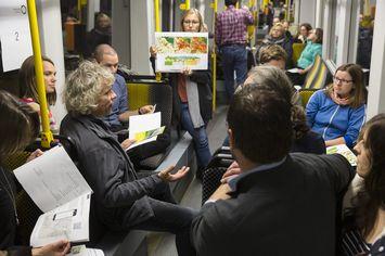 Menschen in der Straßenbahn sitzend, in der Mitte steht eine Frau und hält ein Poster nach obenlt eine